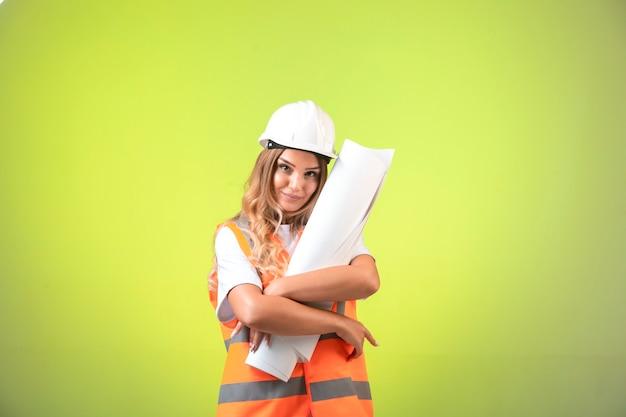 Ingeniera en casco y equipo sosteniendo el plan de construcción.