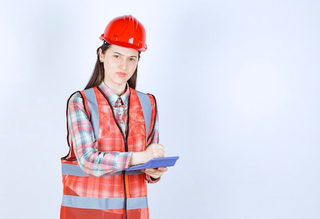 Ingeniera en casco rojo trabajando en calculadora.