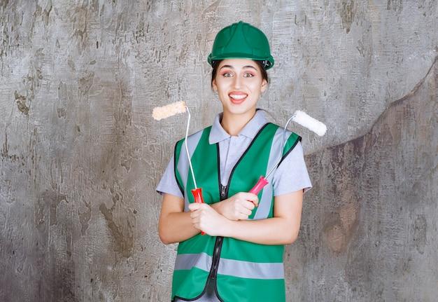 Ingeniera en casco verde sosteniendo un rodillo de ajuste para pintura mural