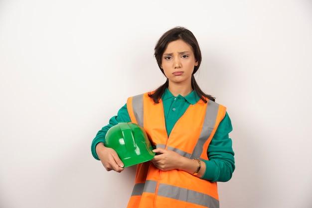Ingeniera frustrada sosteniendo un casco sobre fondo blanco.