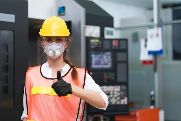 La ingeniera lleva una máscara facial con un chaleco de seguridad y un casco amarillo que muestra los pulgares para arriba en la fábrica.