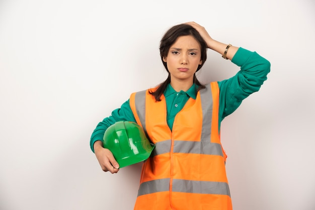 Ingeniera molesta rascándose la cabeza y sosteniendo un casco sobre fondo blanco.