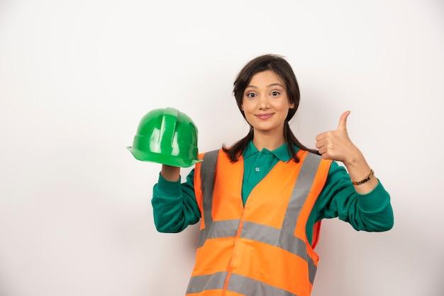 Ingeniera mostrando el pulgar hacia arriba y sosteniendo un casco sobre fondo blanco.