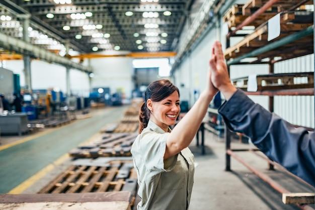 Ingeniera mujer alta cinco con colega en el pasillo de la fábrica.