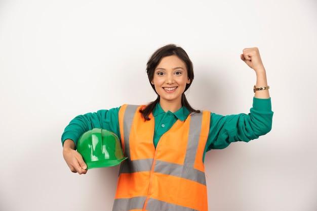 Ingeniera sonriente mostrando los músculos y sosteniendo un casco sobre fondo blanco.