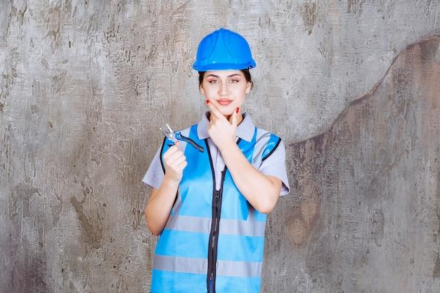 Ingeniera en uniforme azul y casco con alicates metálicos para reparación y se ve pensativa.