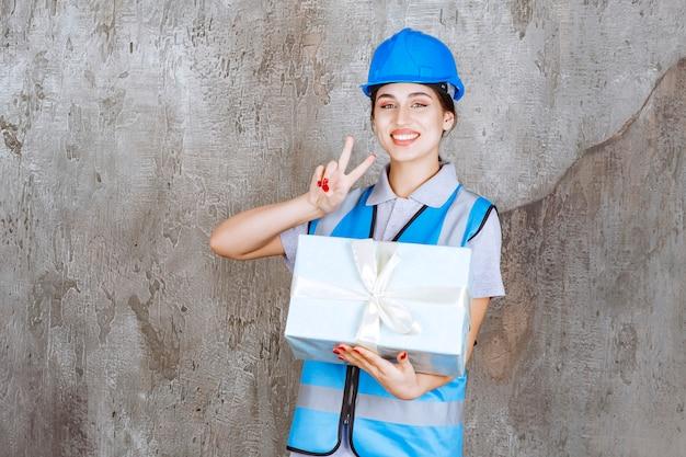 Ingeniera en uniforme azul y casco sosteniendo una caja de regalo azul y mostrando un signo de mano positivo.