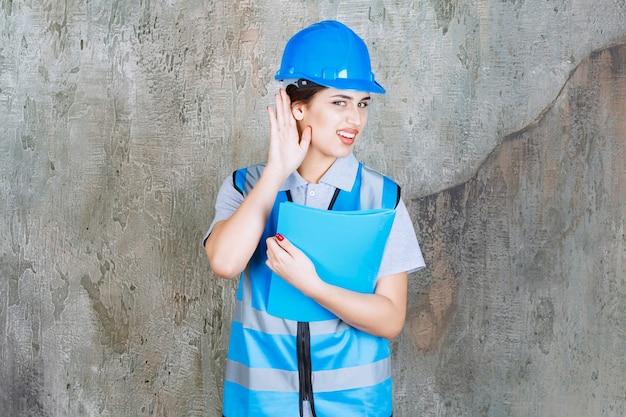Ingeniera en uniforme azul y casco sosteniendo una carpeta de informe azul y abriendo el oído para escuchar bien.