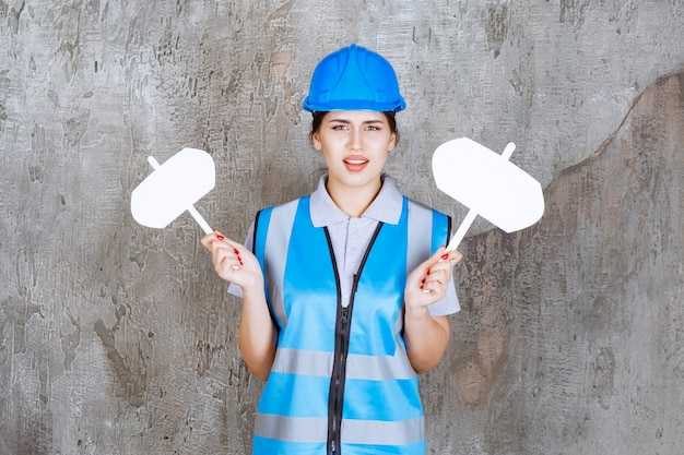 Ingeniera en uniforme azul y casco sosteniendo dos tableros de información en blanco en ambas manos y parece insatisfecho.