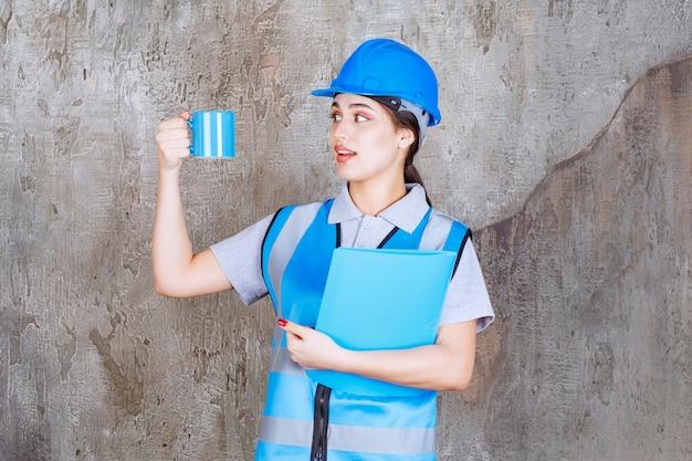 Ingeniera en uniforme azul y casco sosteniendo una taza de té azul y una carpeta de informe azul.