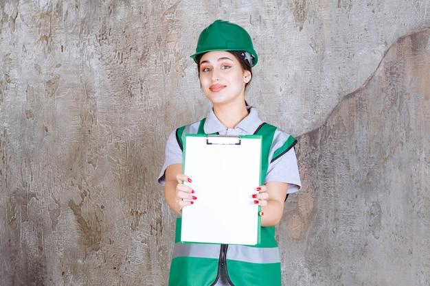Ingeniera en uniforme verde y casco demostrando la hoja del proyecto