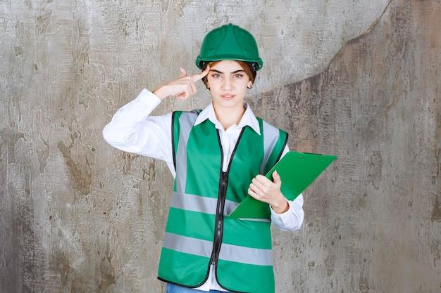 Ingeniera en uniforme verde y casco sosteniendo una carpeta de proyecto verde y pensando.