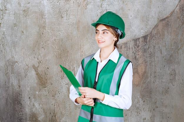 Ingeniera en uniforme verde y casco sosteniendo una carpeta de proyecto verde.