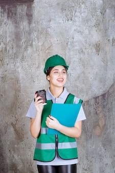 Ingeniera en uniforme verde y casco sosteniendo una taza de café negro y una carpeta de proyecto azul.