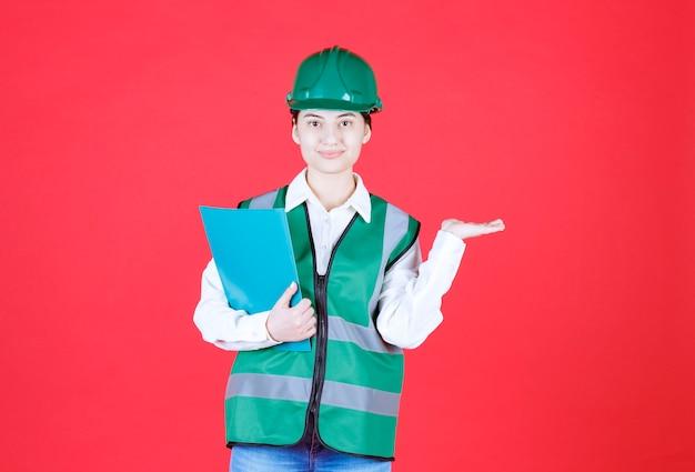 Ingeniera en uniforme verde sosteniendo una carpeta azul y llamando a su colega