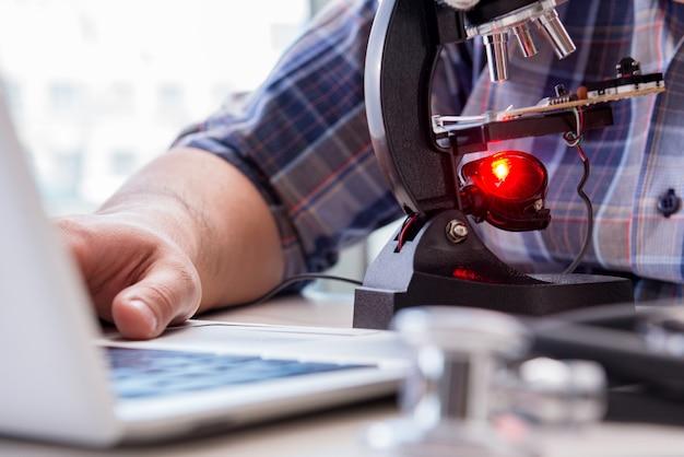Ingeniería de alta precisión con hombre trabajando con microscopio.