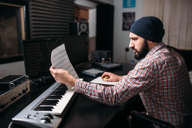 Ingeniería de audio, productor de sonido trabaja con sintetizador en estudio. tecnología de medios digitales profesionales