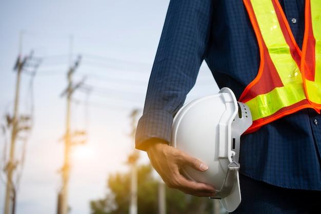 Ingeniería sostiene sombreros de seguridad blancos y poste eléctrico.