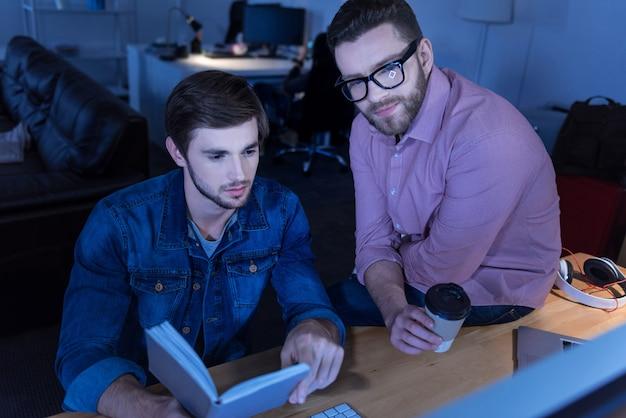 Ingeniería técnica. hombres guapos positivos serios sentados frente a la pantalla de la computadora y concentrados en su proyecto mientras trabajan en la oficina
