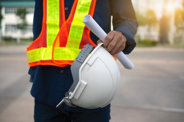Ingeniería tiene sombreros de seguridad blancos y fondo de poste eléctrico