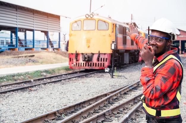 Ingeniero africano levantó una mano para controlar el tren en ferrocarril hablando por radio o walkie talkie