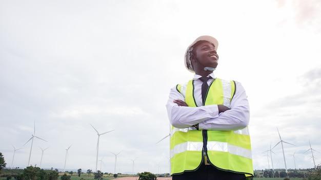 Ingeniero africano de pie con turbina eólica