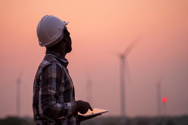 Ingeniero africano que lleva el casco blanco que se coloca con la tableta digital contra la turbina de viento en día asoleado