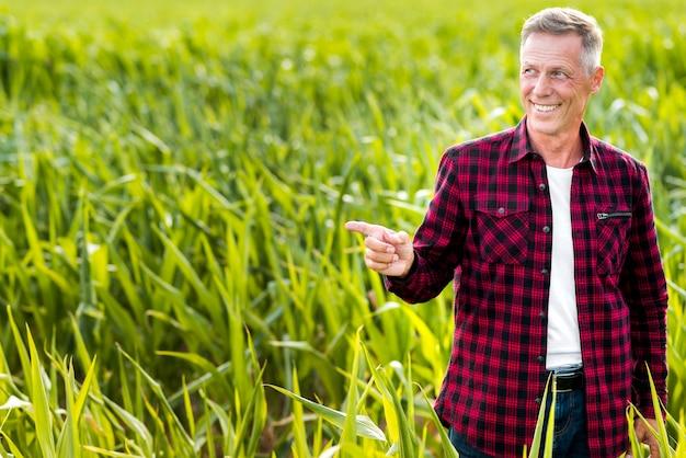 Ingeniero agrónomo sonriente que indica de lado
