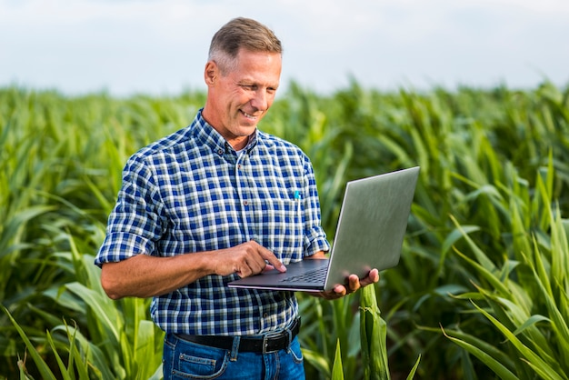 Ingeniero agrónomo sonriente usando una computadora portátil