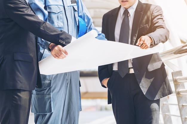 Ingeniero, arquitecto, hombre de negocios discuten en el dibujo.