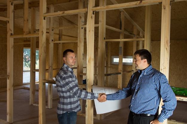 Ingeniero y arquitecto masculino mostrando un apretón de manos en el sitio de construcción, enfatizando que ambos acordaron el diseño del proyecto.