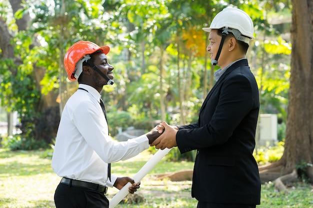 El ingeniero asiático y africano del arquitecto sacude las manos con sonrisa en naturaleza verde.