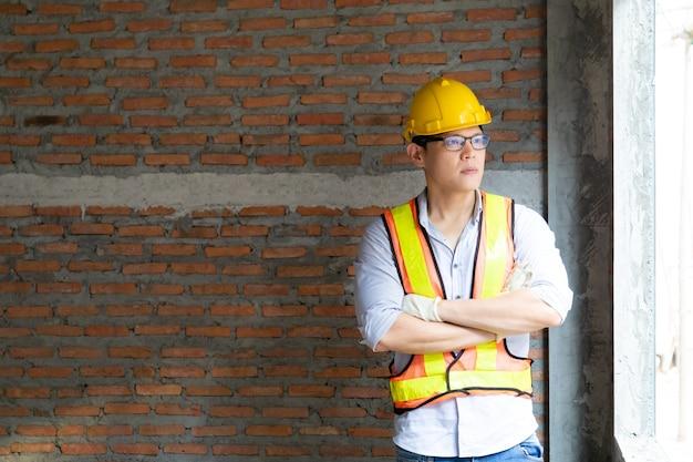 Ingeniero asiático atractivo que trabaja en el sitio de construcción. concepto de trabajador de la construcción.
