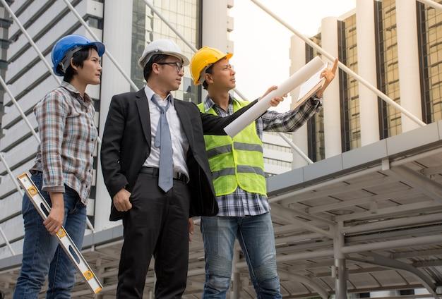 Ingeniero asiático y equipo de arquitectos que comprueban la construcción en el sitio de construcción