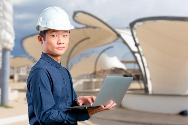 Ingeniero asiático del hombre con el ordenador portátil
