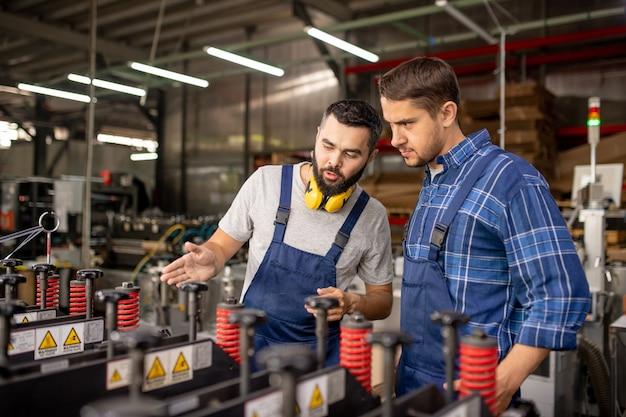 Ingeniero barbudo explicando los principios de trabajo de un colega de nuevos equipos de procesamiento de trabajo suring