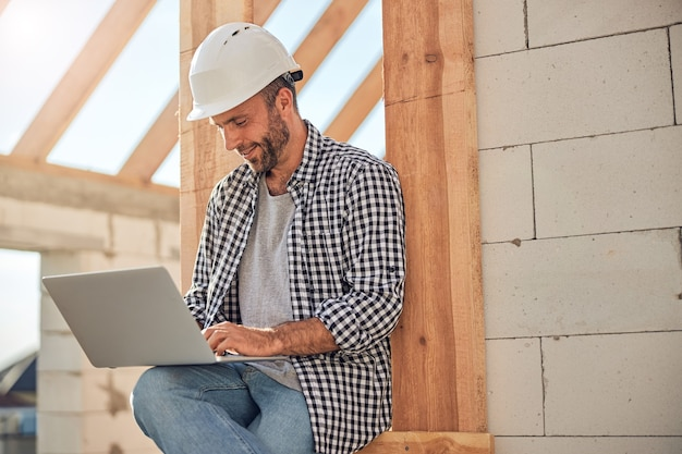 Ingeniero de campo ambicioso que trabaja en su computadora portátil cerca de un edificio