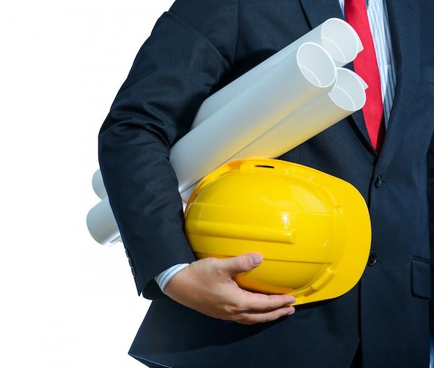Ingeniero casco amarillo para seguridad de trabajadores con planos de construcción aislados.