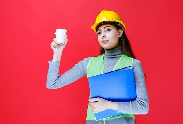 Ingeniero en casco amarillo sosteniendo una carpeta azul y una taza de bebida.