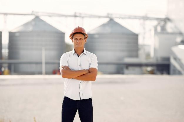 Ingeniero en un casco parado junto a la fábrica