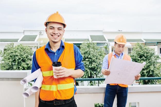 Ingeniero civil alegre tomando café