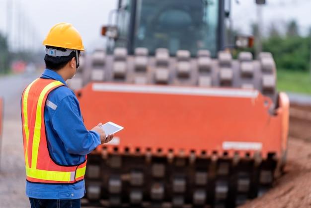 El ingeniero civil asiático usa un casco en el sitio de construcción de carreteras.