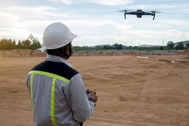 Ingeniero civil controla el dron para inspeccionar trabajos de construcción