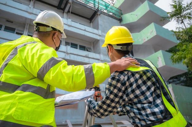 El ingeniero civil del equipo de encuesta está trabajando con un telescopio de encuesta en el sitio de construcción. uso de telescopio topográfico para trabajos de construcción en sitios de construcción. ingeniero civil con telescopio en la encuesta.