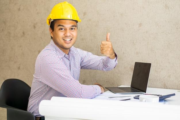 Ingeniero civil felicidad y mostrar pulgar arriba trabajando en la oficina.