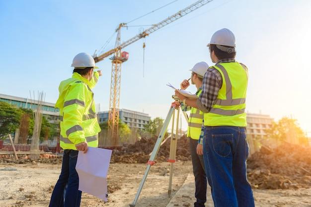 El ingeniero civil inspecciona el trabajo mediante comunicación por radio con el equipo directivo en el área de construcción.