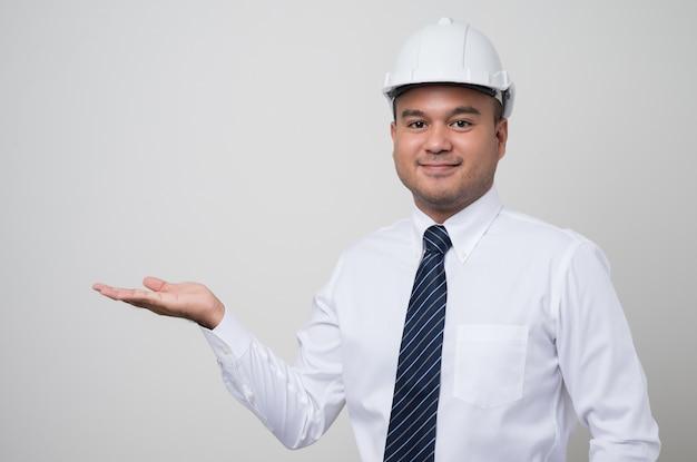 Ingeniero civil mostrando la palma de la mano al espacio en blanco.