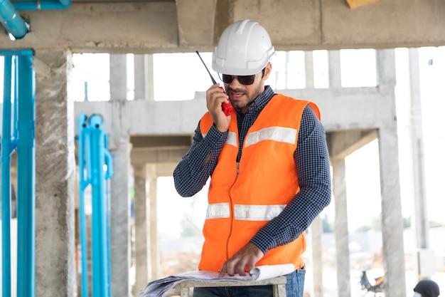 Ingeniero civil de oriente medio operar trabajador en radio para controlar el trabajo en el sitio de construcción