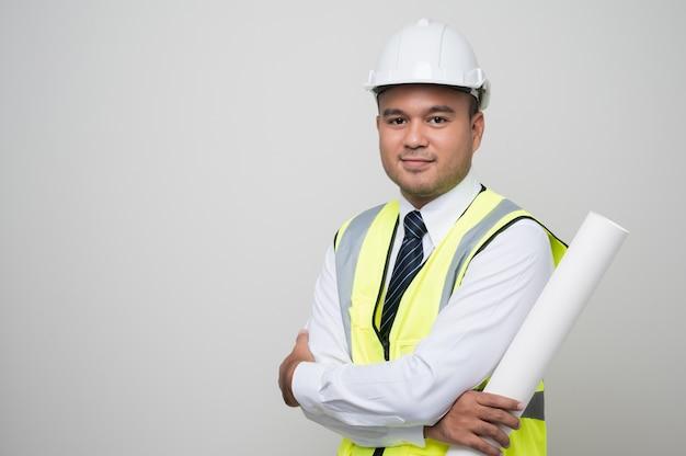 Ingeniero civil que sostiene el poste permanente del rollo del modelo del papeleo en estudio.