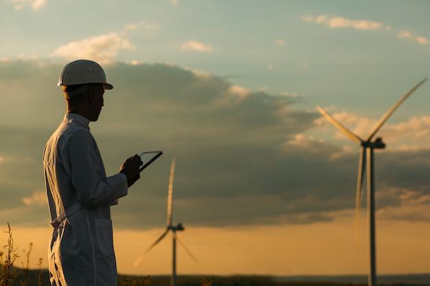 El ingeniero comprueba el sistema de turbina eólica con una tableta. energía alternativa. granja eólica. tecnologías limpias de energía renovable. plantas de energía eólica.